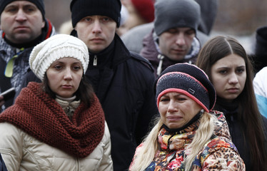 People mourn at the site where anti-Yanukovich protesters have been killed in recent clashes in Kiev