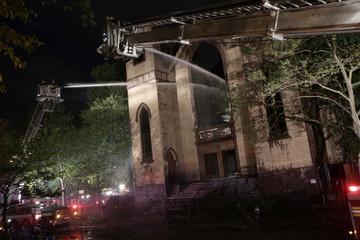 Firemen spray the burned Beth Hamedrash synagogue in New York City