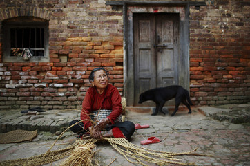 """A woman weaves a traditional carpet, also known as """"sukul"""" in Nepali, using dried hay in Lalitpur"""