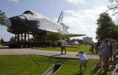 "A couple has their picture taken with the Space Shuttle replica ""Explorer"" in the background during its move along NASA Parkway to the Lyndon B. Johnson Space Center in Houston"