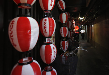 A man walks past paper lanterns displayed on a wall of a restaurant in Tokyo