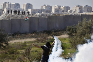 A Palestinian stone-throwing protester uses a sling to throw back a tear gas canister fired by Israeli security officers during clashes near Ramallah