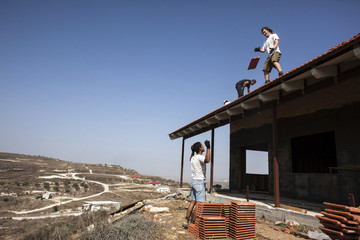 Men work on the roof of a house under construction in the unauthorised Jewish settler outpost of Havat Gilad, south of Nablus