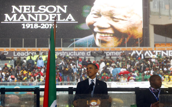 U.S. President Obama gives a speech as a man passing himself off as a sign language interpreter folds his hands during a memorial service for late South African President Nelson Mandela in Johannesburg
