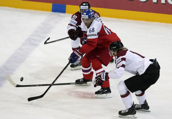 Jagr of the Czech Republic fights for the puck with Latvia's Jass and Abols during their Ice Hockey World Championship game at the O2 arena in Prague