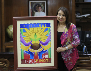 Ma. Josefina Dela Cruz, the Philippine postmaster general, poses with a copy of a Haiyan stamp inside the post office in Manila