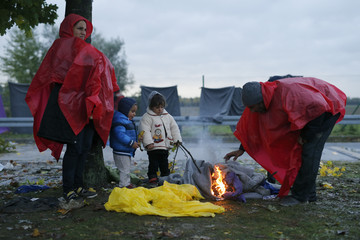 Migrants warm themselves next to a fire as they wait to cross the border with Slovenia near Trnovec