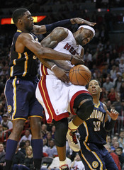 Miami Heat's James is fouled by Indiana Pacers Hibbert as the Pacers Granger looks on during fourth quarter NBA basketball action in Miami