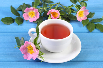 Cup of tea and wild rose flower on boards