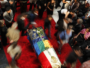 The body of Mexican writer Monsivais lies in a coffin as people mourn during his wake at Bellas Artes museum in Mexico City