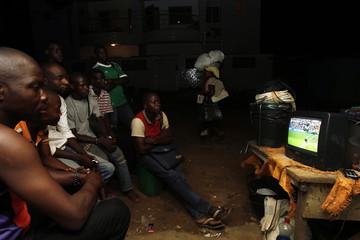People watch the 2014 World Cup Group F soccer match between Nigeria and Iran on a street in Abidjan