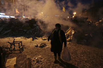 A woman stands at a barricade erected by anti-government protesters near the site of clashes with riot police in Kiev