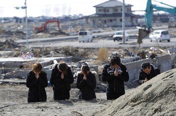 People pray for a family member who was killed in the March 11, 2011 earthquake and tsunami, during the first anniversary of the disaster, in Ishinomaki