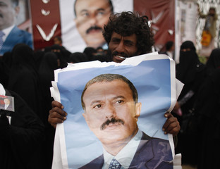 A man holds a poster of Yemen's former President Ali Abdullah Saleh outside al-Saleh mosque after weekly Friday prayers in Sanaa