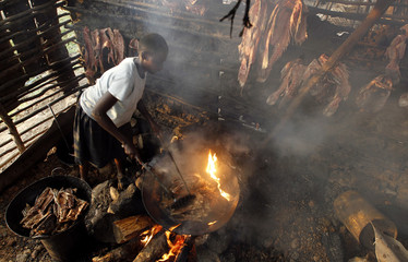 "A fish trader fries fish skeletons inside her stall at the Obunga ""mgongo-wazi"" fish frying market in Kisumu"