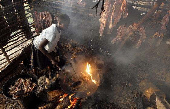 "A fish trader fries fish skeletons inside her stall at the Obunga ""mgongo-wazi"" fish frying market in Kisumu"