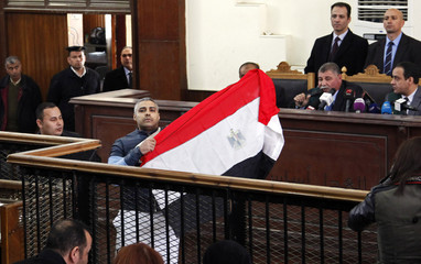 Al Jazeera journalist Mohamed Fahmy raises Egyptian national flag while talking to judge during retrial at court in Cairo