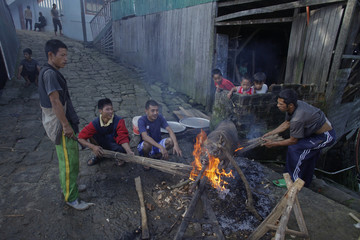 Villagers roast a pig for lunch for Ziona's family