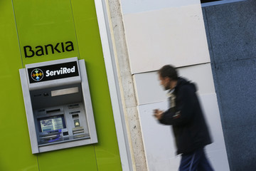 A man walks past an automated teller machine of Spain's nationalized lender Bankia in Madrid