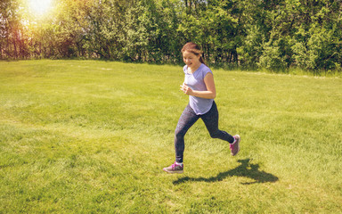 A young girl is running on grass