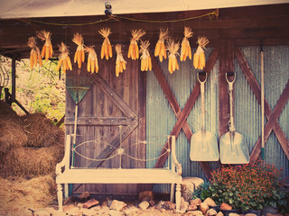 Old chair, gardening tools in front of barn, vintage filter effect