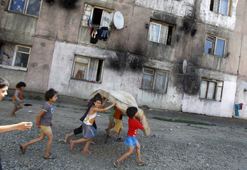 Ethnic Roma children play near an apartment block in a wall surrounded Roma neighbourhood at Romania's northern town of Baia Mare