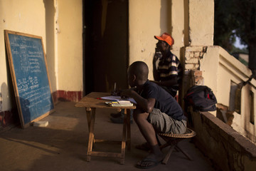 Boy looks at a chalkboard as he attends home tuition at a house built during the French colonial times in a neighbourhood of the capital Bangui