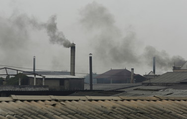 Smoke rises from the chimney of a paper factory in Phong Khe village, outside Hanoi