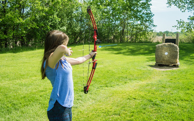 A young girl is practicing archery, the moment of releasing the arrow