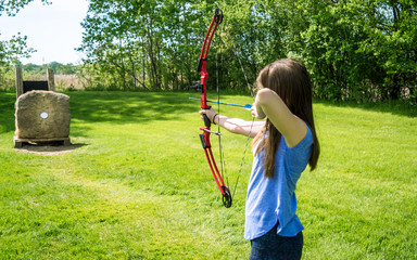 A young girl is practicing archery