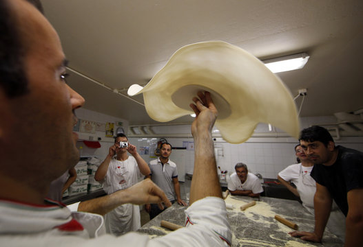 Nabil Berrahmane, free style world chmapion, demonstrates how to throw pizza dough during an acrobatic pizza course at the French pizzaiolo school, in Cap D'Ail