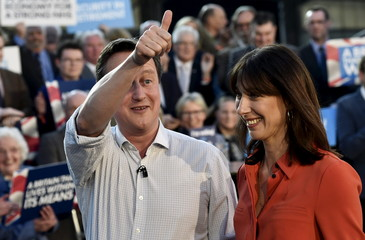 Britain's Prime Minister Cameron gestures to the crowd as he walks with his wife Samantha after delivering a speech to Conservative Party supporters and activists during an election campaign event in Wadebridge,
