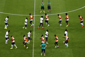 Members of Ivory Coast's national soccer team warm up during a training session at the Arena Pernambuco soccer stadium in Recife