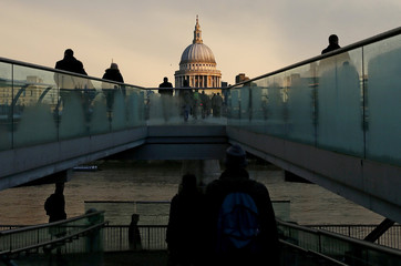 File photo of city workers walking towards St Paul's Cathedral as they cross the Millennium footbridge during sunrise in central London