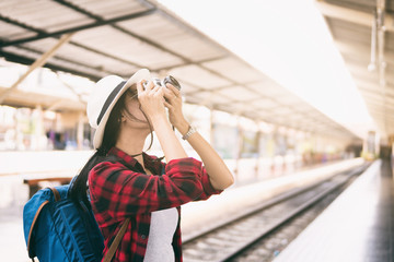woman traveler holding camera for taking photograph on train station,travel alone lifestyle concept,woman travel,sun flare effect and vintage tone.