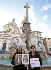 Members of support group for clergy abuse victims SNAP, Lucy Duckworth and Joelle Casteix, hold photos of young victims as they protest in Rome's Navona Square