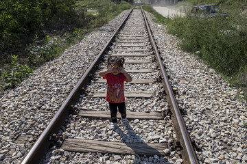 A migrant child, whose family hopes to cross into Hungary, covers her face with her hands as she walks along a railway track outside the village of Horgos in Serbia, towards the border it shares with Hungary