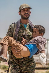 A Kurdish People's Protection Units fighter carries an injured boy as they make their way towards the Turkish border in Tel Abyad town