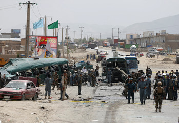 Afghan security forces inspect the damage on buses hit by suicide bombers at the site of an attack in Kabul, Afghanistan