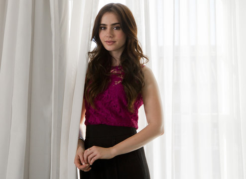 "Actress Lily Collins, who stars as Snow White in the film ""Mirror Mirror"", poses for Reuters in Santa Monica"