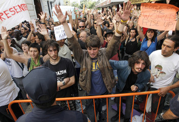 Demonstrators raising their hands and shouting slogans are prevented by police from getting close to the regional parliament in Valencia