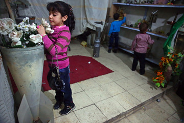 Children play with ornamental objects made from remnants of weapons at a basement in the Duma neighbourhood in Damascus