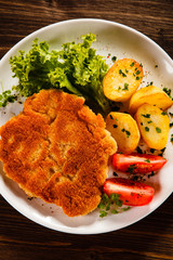 Fried pork chop with potatoes on wooden table