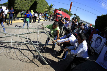 Activists and relatives of the 43 missing trainee teachers from Ayotzinapa's teacher training college pull a barbed wire during a demonstration at the military zone of the 27th infantry battalion in Iguala, Guerrero