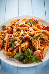 Pasta with tomato sauce and parmesan on blue planks