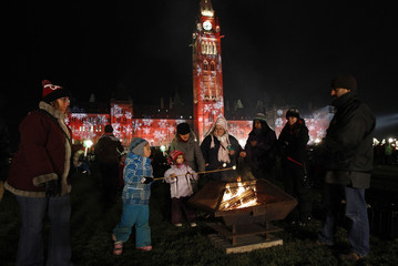 People roast marshmallows during a Christmas light illumination ceremony on Parliament Hill in Ottawa