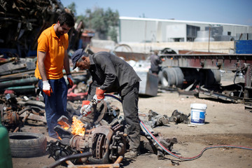 A worker cuts car parts for the Jordanian graphic designer Abdelrahman Asfour, who turns car parts into furniture, at a junkyard in Amman