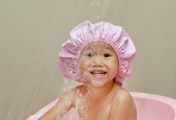 happy little child in a cap of foam in bath.