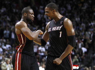 Miami Heat's Wade and Bosh celebrate after scoring against the Los Angeles Lakers in Miami