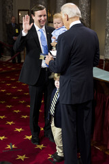 Senator Chris Murphy holds his son Rider as he takes part in a mock swearing in ceremony with U.S. Vice President Joe Biden in the Old Senate Chamber on Capitol Hill